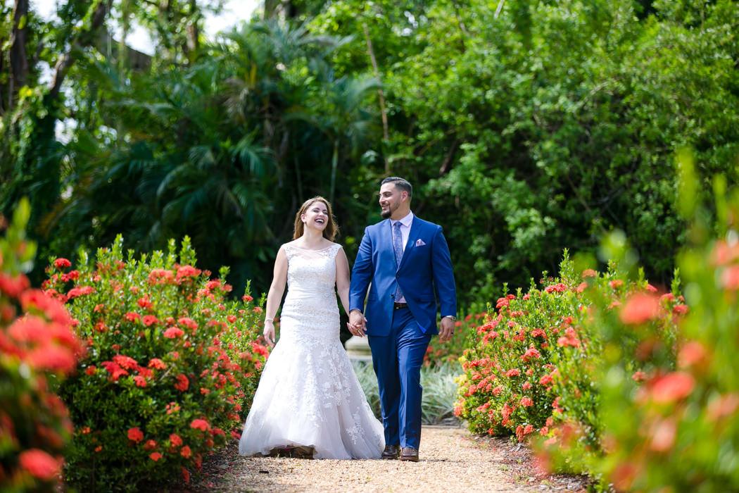 bride and groom walking through gardens of ancient spanish monastery miami | ancient spanish monastery wedding