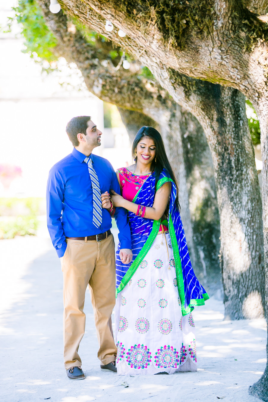 Indian couple laughing as they walk through vizcaya in miami on engagement photoshoot
