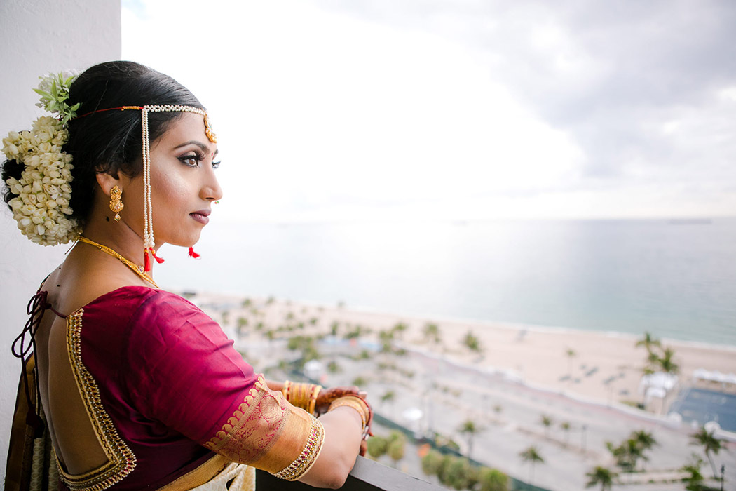 indian bride wearing gold and red sari on her south florida wedding day at bahia mar fort lauderdale