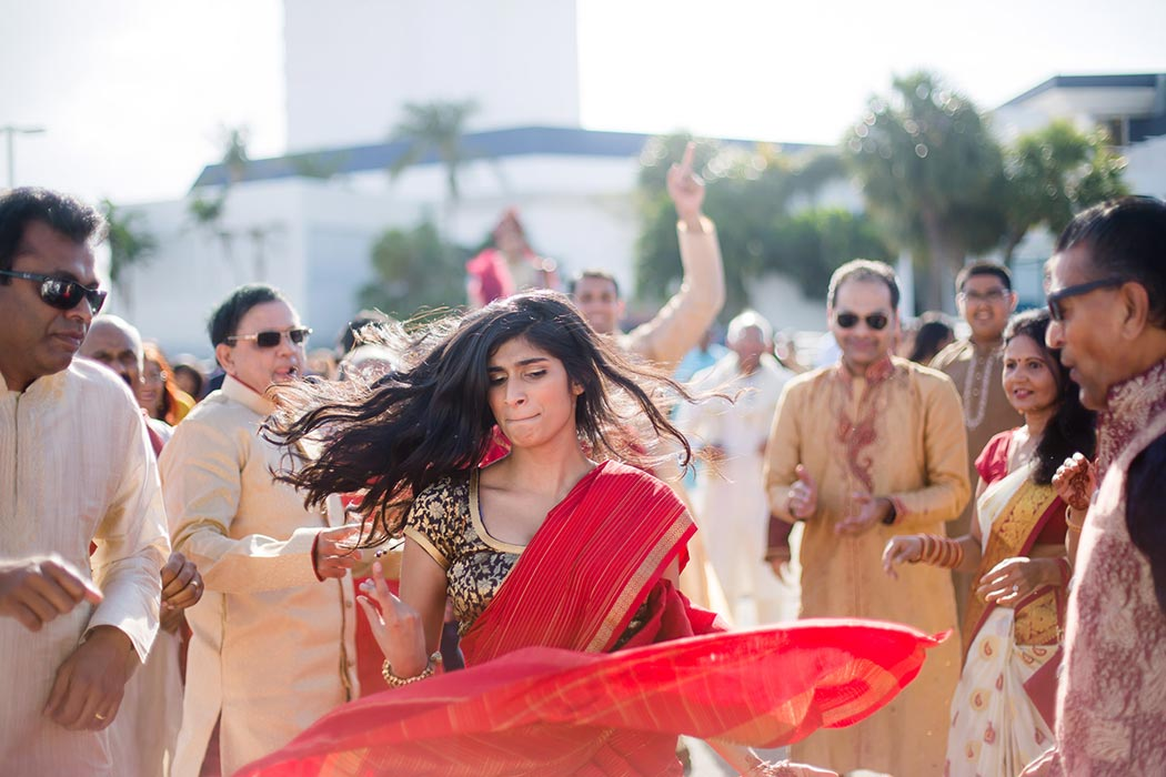 girl in red sari dances during south florida indian baraat celebrations