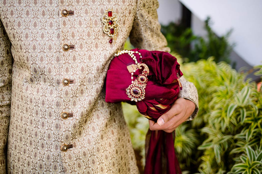 traditional indian groom poses in gold suit with red turban | fort lauderdale indian wedding photographer