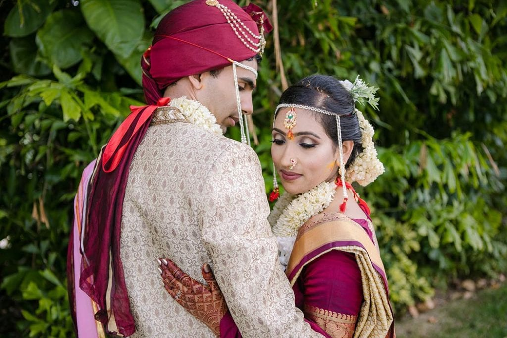indian bride and groom pose for wedding photograph