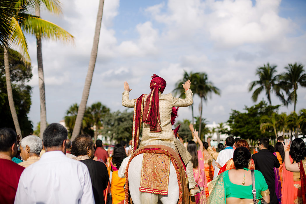 indian groom on white horse during baraat at bahia mar fort lauderdale