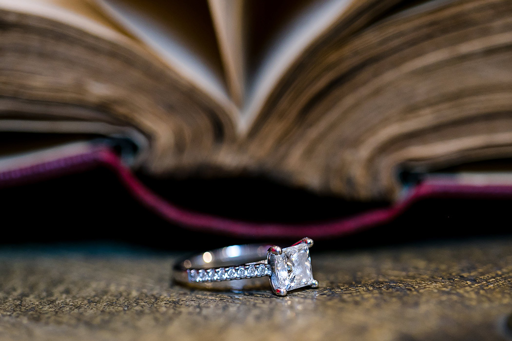 diamond engagement ring photographed next to antique book in engagement session