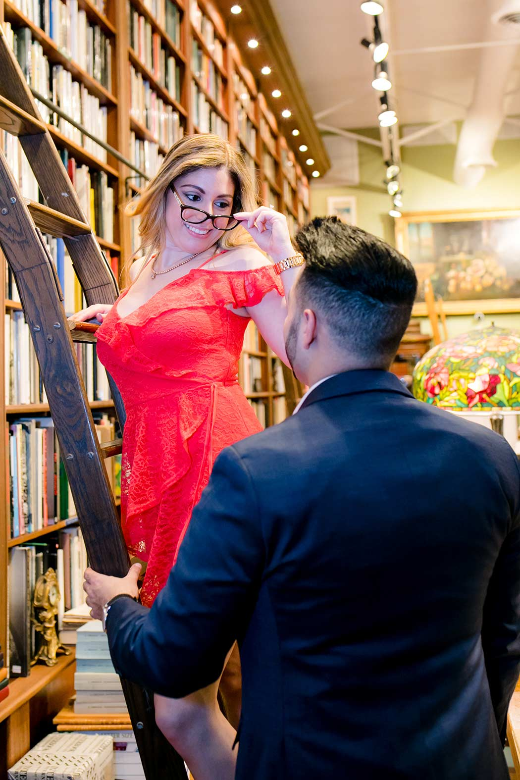 couple pose on library ladder in book store for their engagement session | fort lauderdale engagement photographer