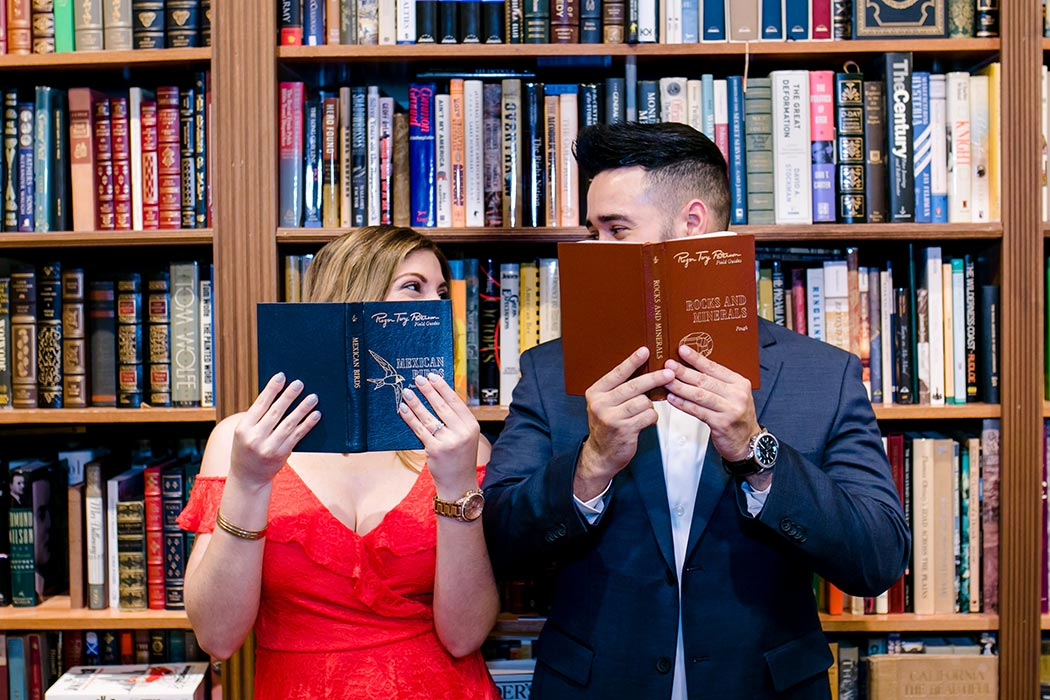 couple posing behind some antique books for their engagement session in fort lauderdale