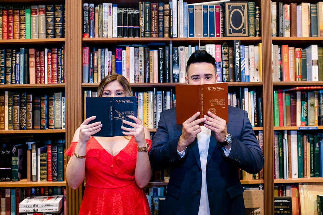 couple posing for their engagement session in an antique book shop
