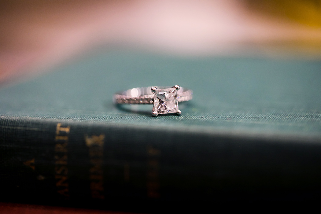 square diamond engagement ring is photographed on an antique book during engagement session