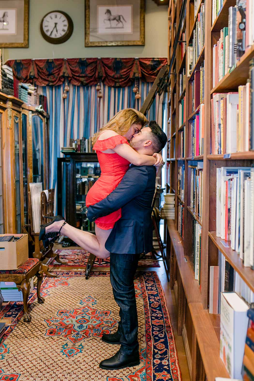 couple embrace for a flirty engagement session in old florida book shop