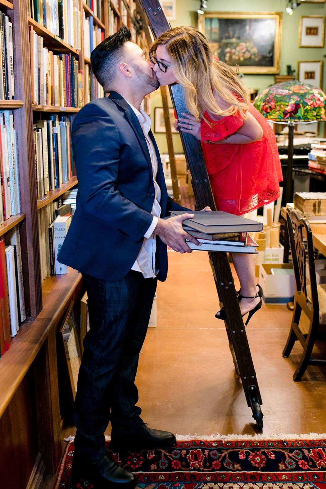 couple kiss in book store for their engagement session on library ladder