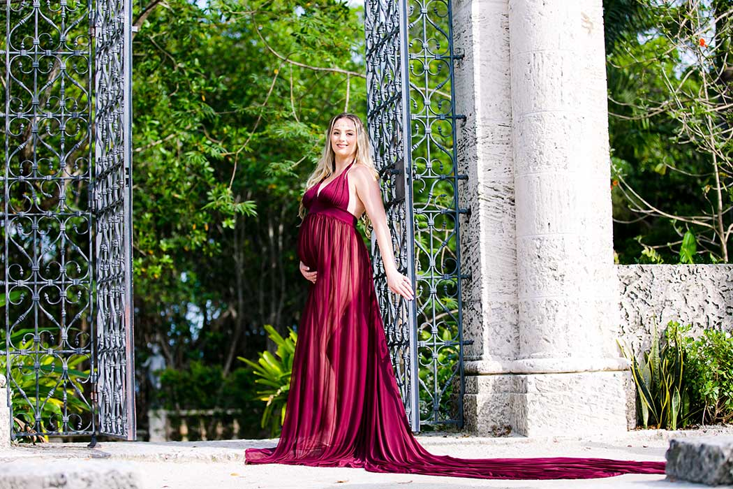 pregnant lady poses with iron gate at vizcaya museum in miami wearing long red maternity dress