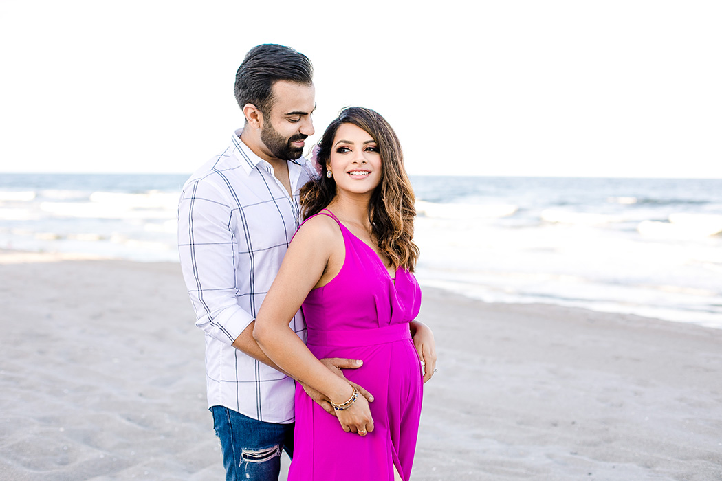 couple posing on the beach for a beach maternity photography session wearing pink maternity dress
