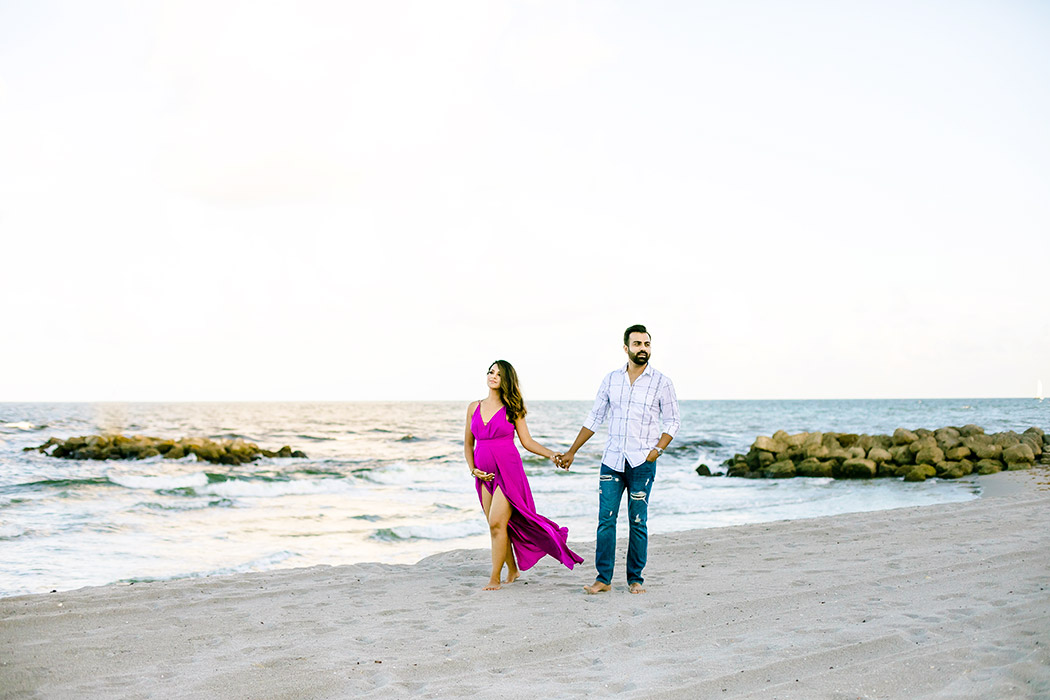 couple walk on fort lauderdale beach during maternity photoshoot   pink maternity dress