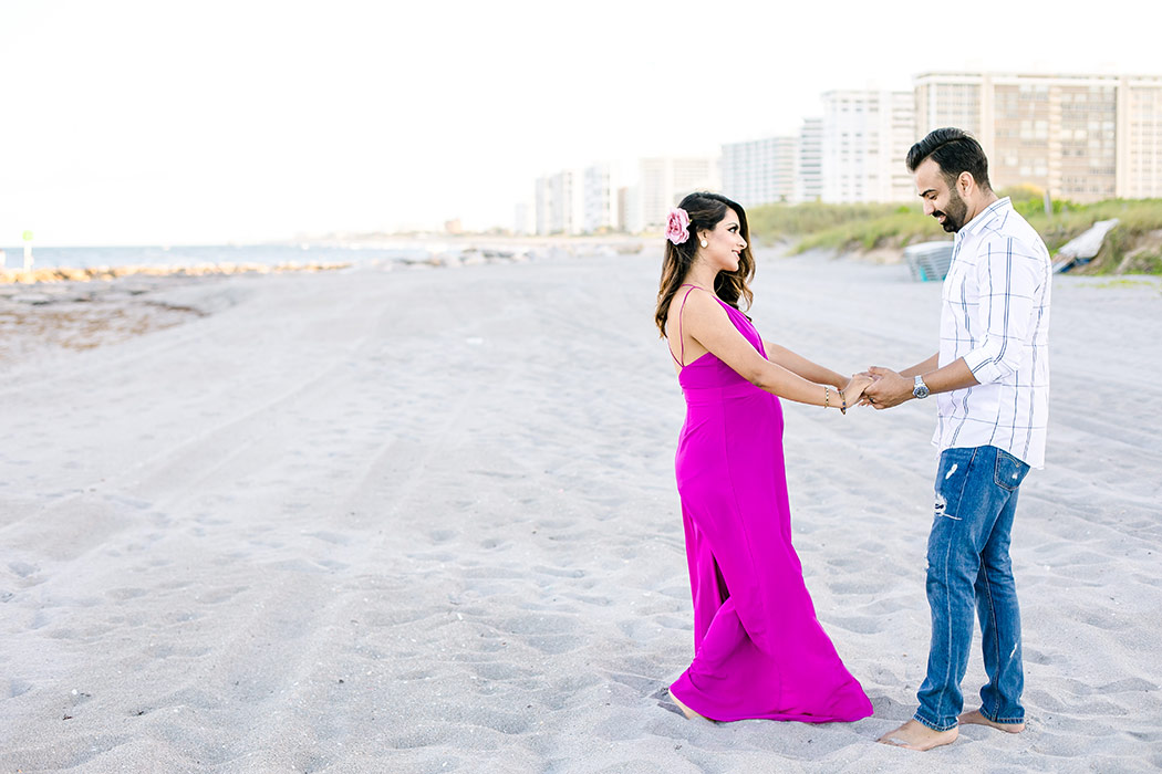 girl in pink maternity dress dances with husband on beach during beach maternity session in boca raton