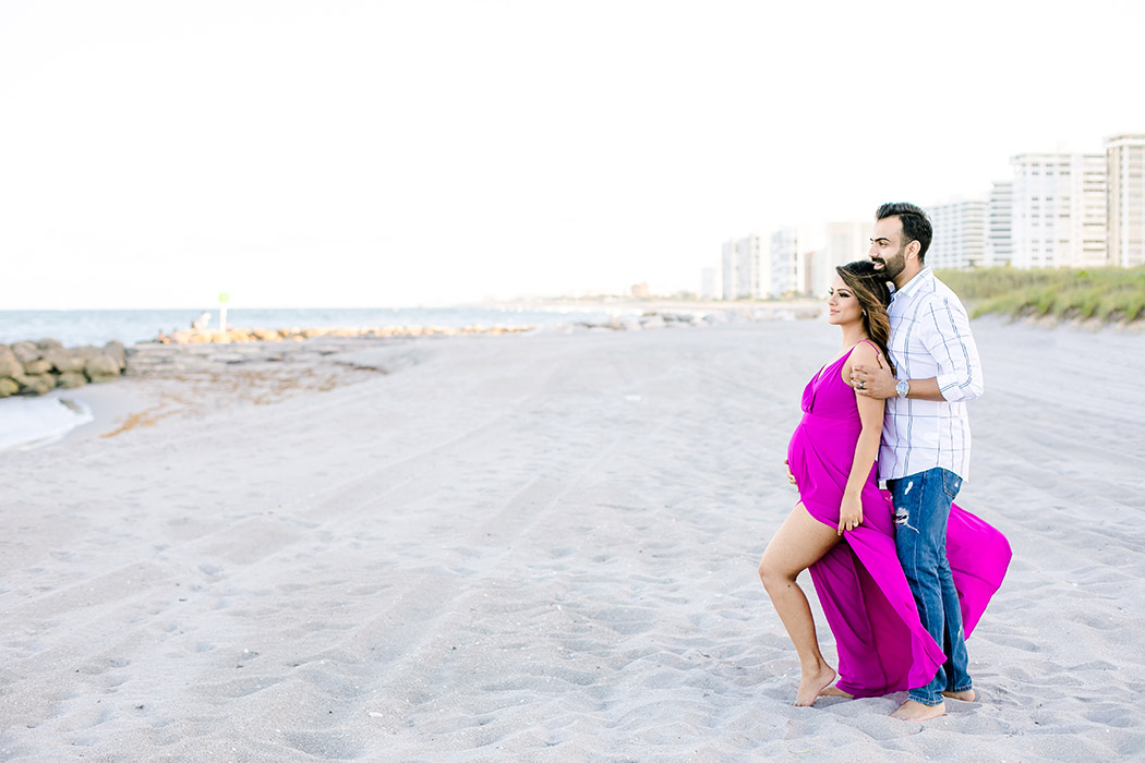 beach maternity photoshoot with couple looking out to sea   pink maternity dress