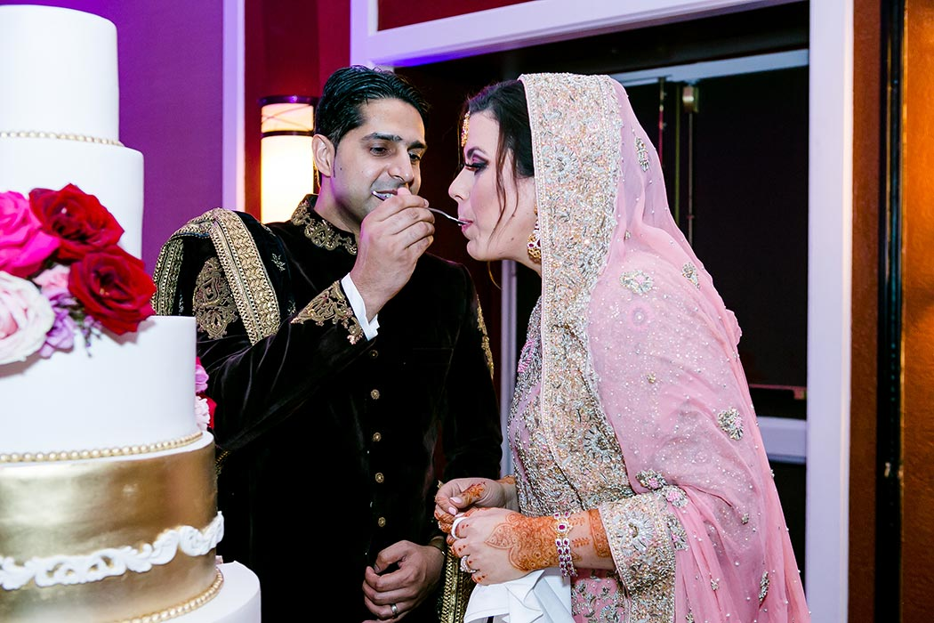 indian bride and groom portraits whilst eating their wedding cake