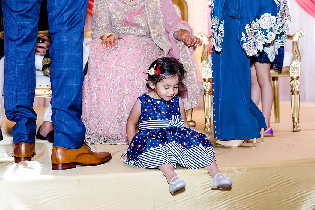 little indian girl in blue and white dress on the stage of indian bride and groom wedding reception