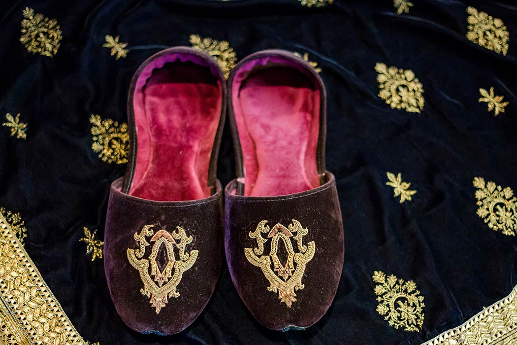 photograph of indian groom's purple and gold wedding shoes | groom purple and gold velvet wedding shoes