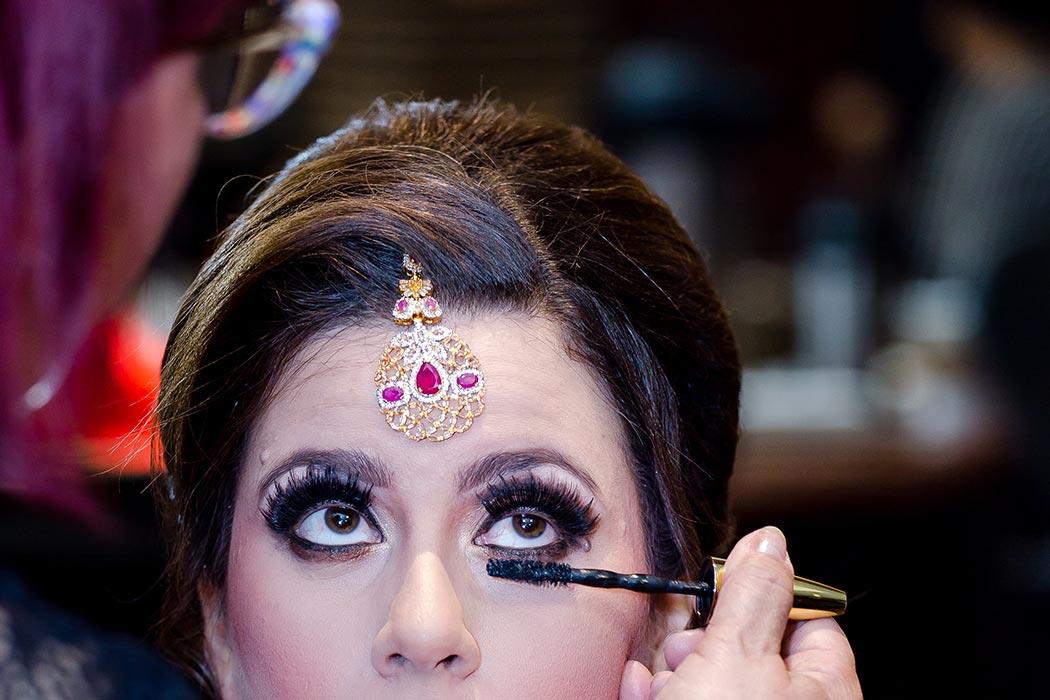 indian bride having her makeup done before her muslim indian wedding ceremony