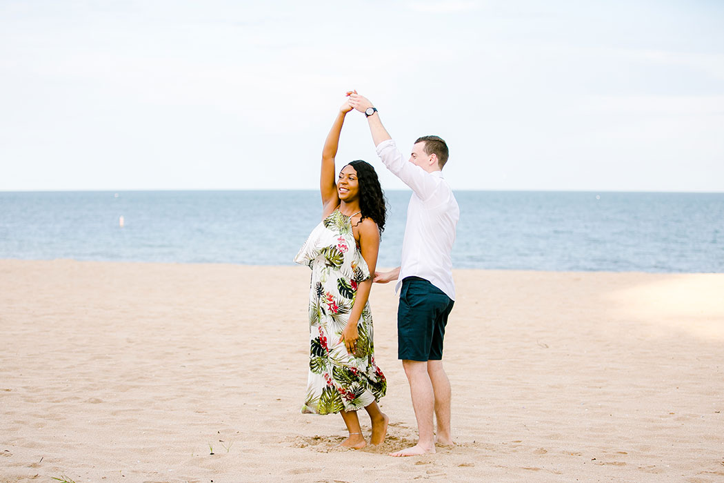 mixed race couple dancing on pompano beach during engagement photoshoot | beach engagement photographer south florida