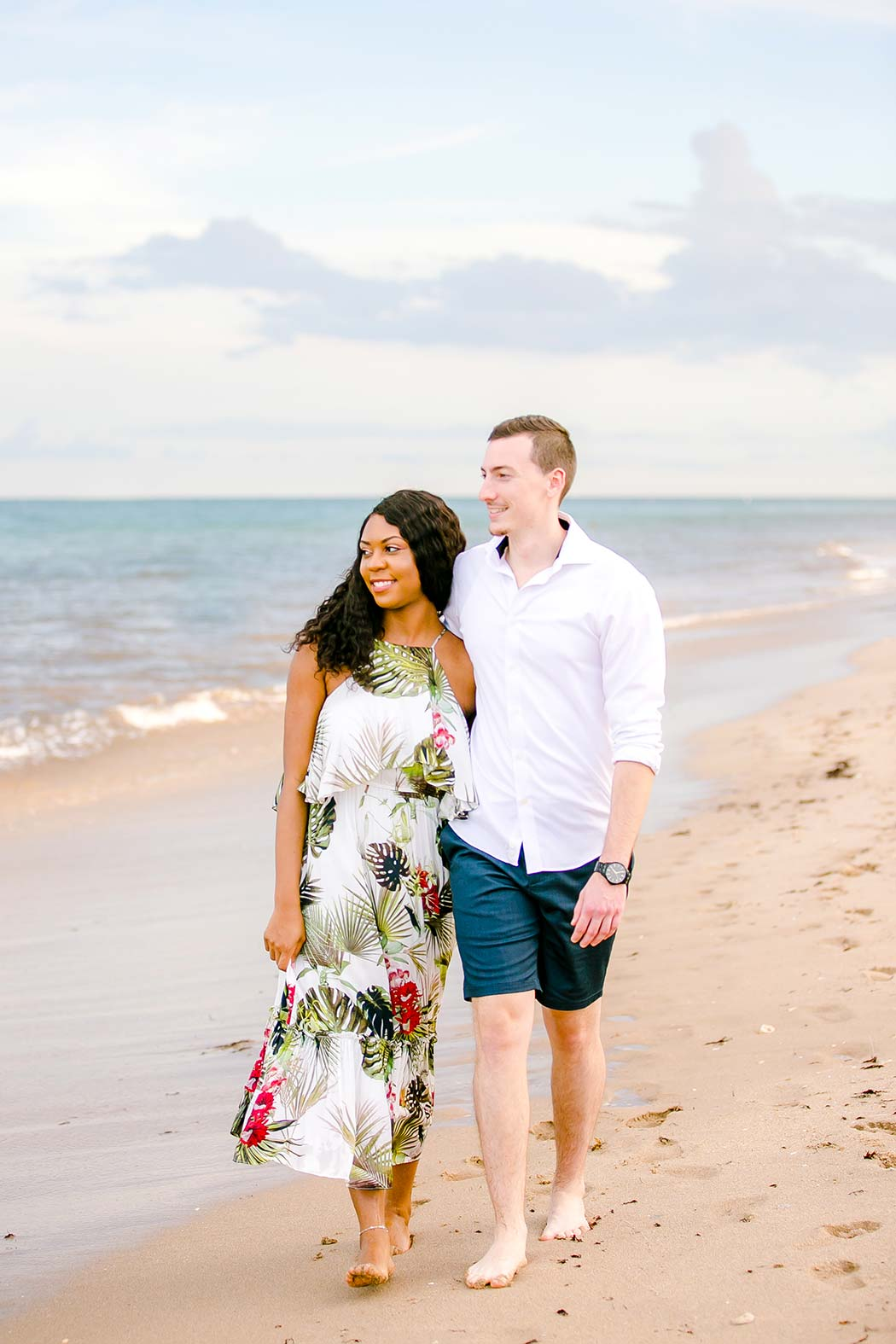 gorgeous mixed race couple pose on beach during engagement session at pompano beach south florida