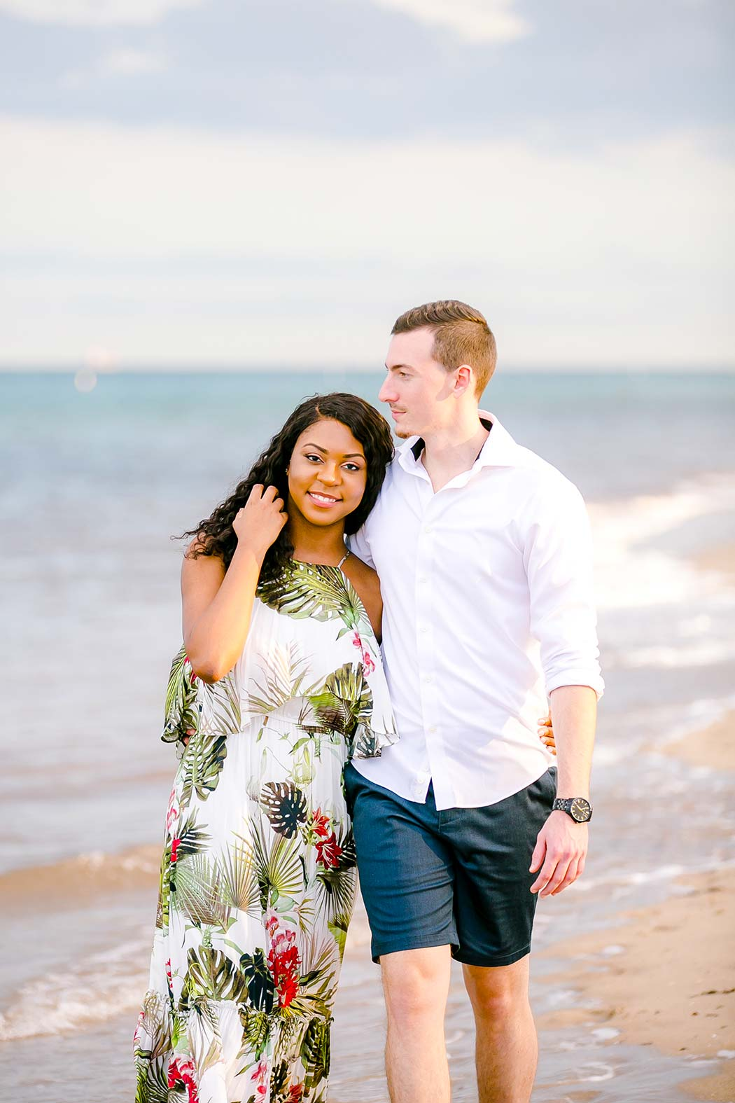 beautiful mixed race couple walking on beach for engagement photoshoot