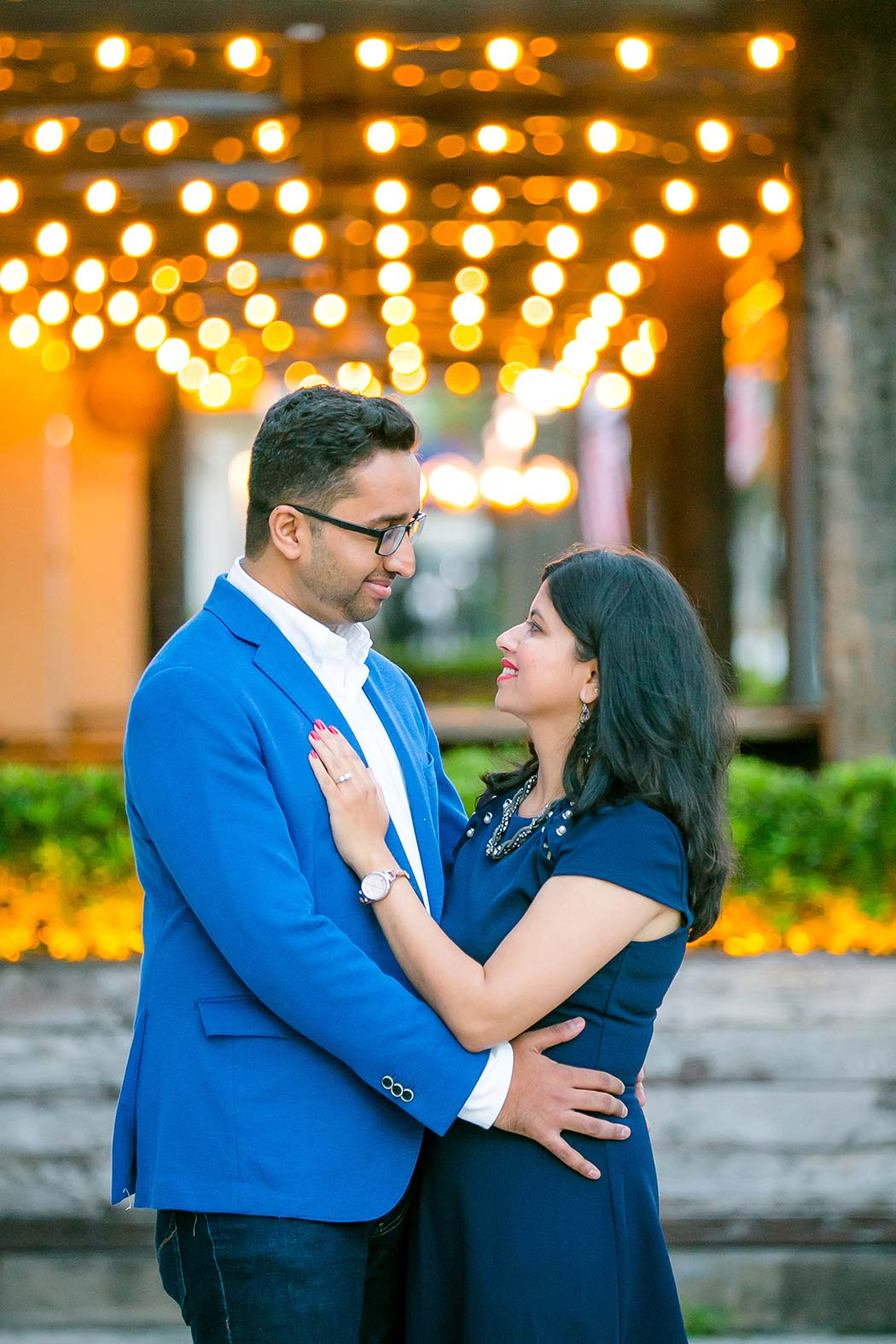 indian couple pose for family photography on las olas boulevard with lights