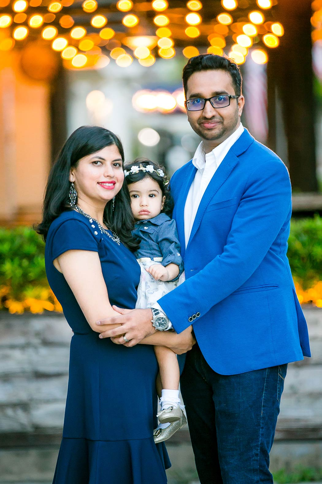 family poses with young baby for family photographs in fort lauderdale | family photography with string lights