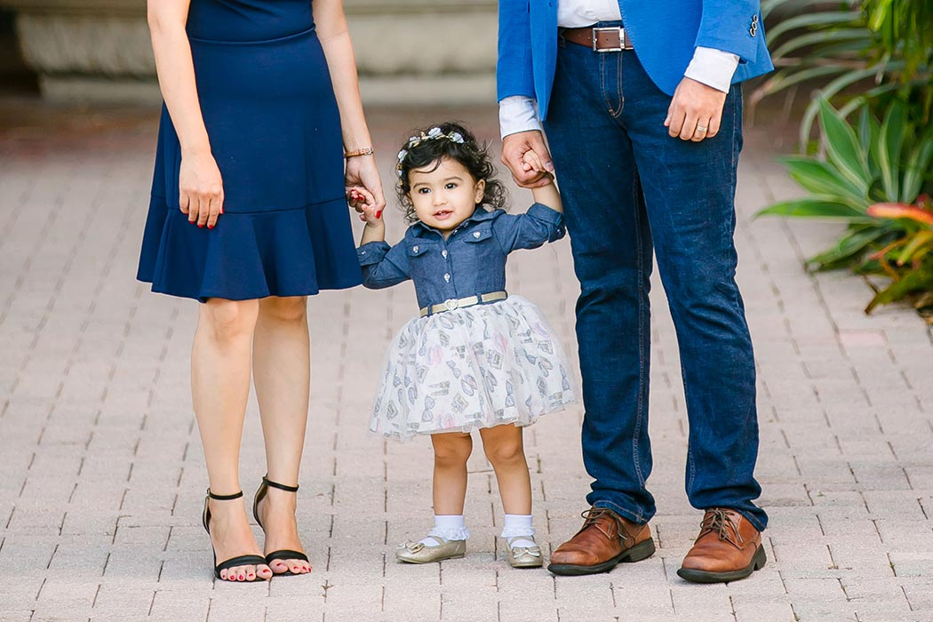 couple holding hand of young child during family photography session on las olas boulevard | fort lauderdale family photographer